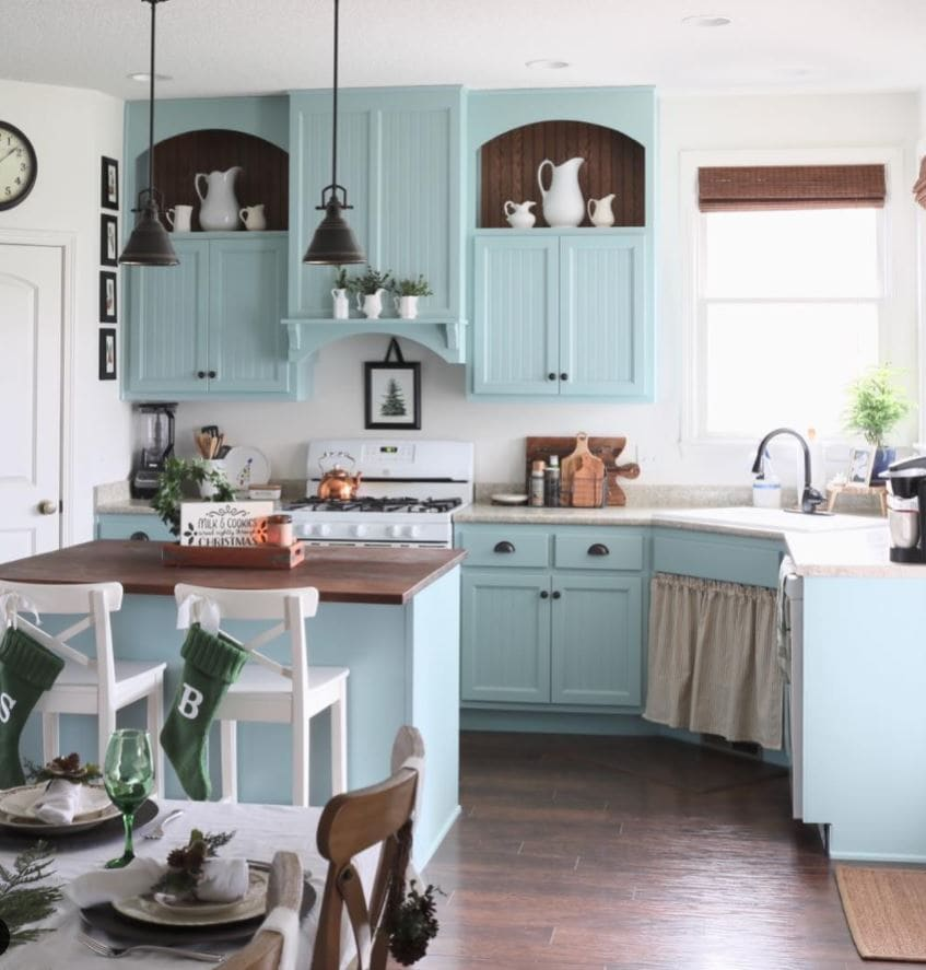 A cozy cottage kitchen with blue cabinets decorated for the holidays.
