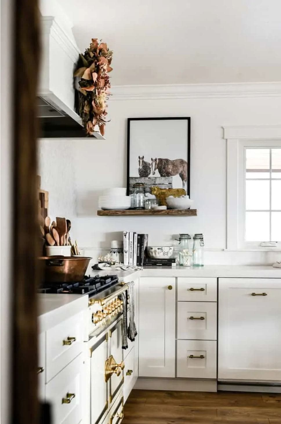 A farmhouse kitchen with a French range and white shaker cabinets.
