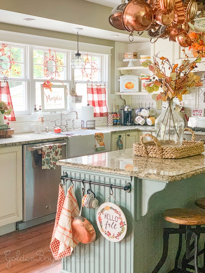 A cottage kitchen with blue/green island and colorful fall décor.