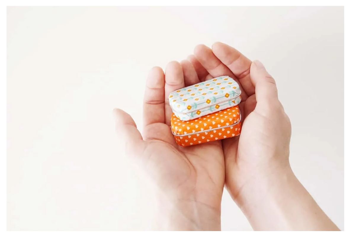 Hands holding two mint tins that have been decorated with washi tape.