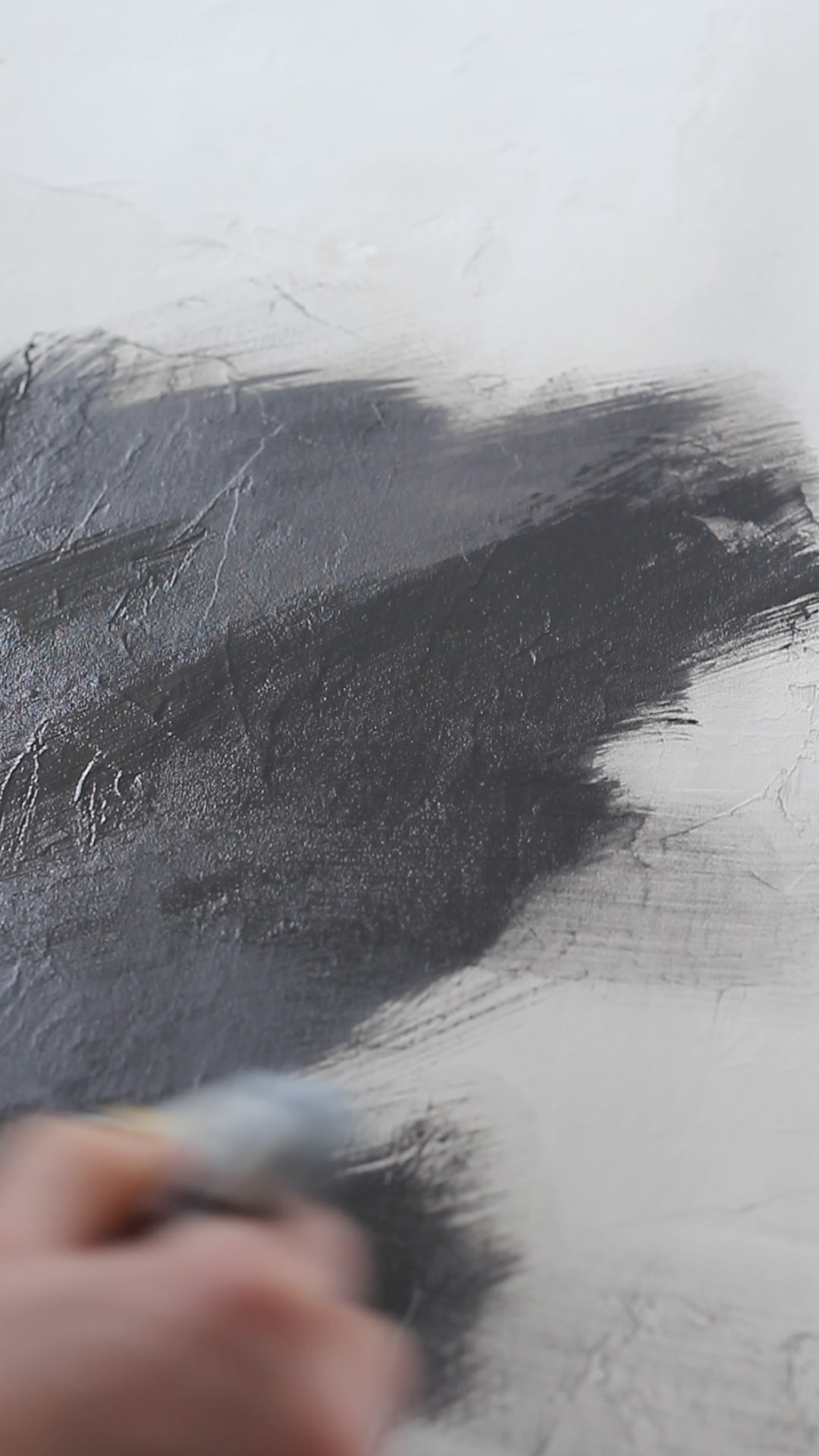 Painting black paint onto a light background.