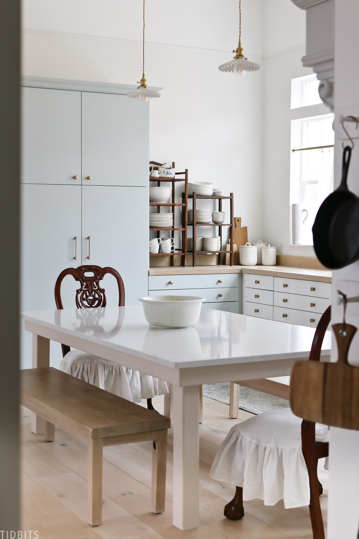 A European kitchen with subtle blue cabinetry and antique décor.