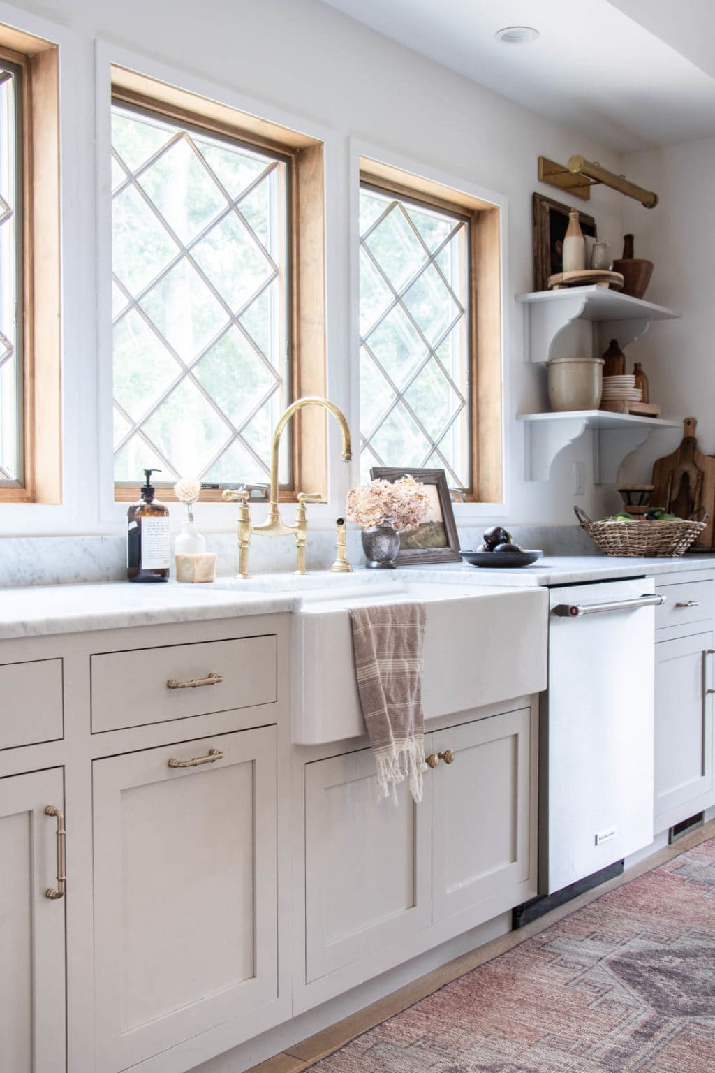 An apron sink with neutral cabinets and diamond pane windows.