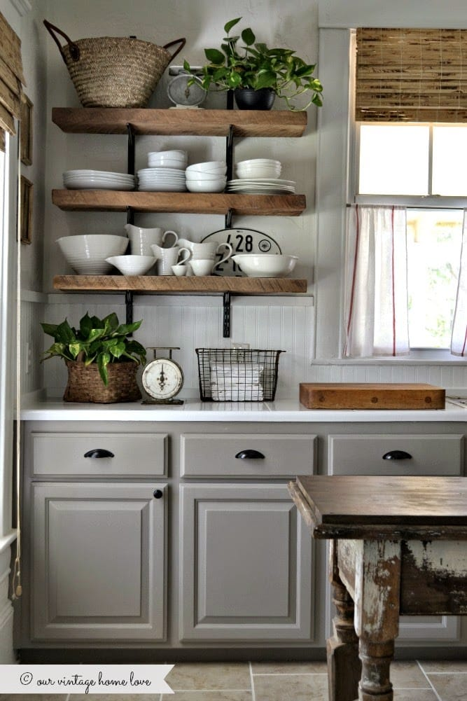 A farmhouse style kitchen with gray cabinets, open shelving, and white dishes.