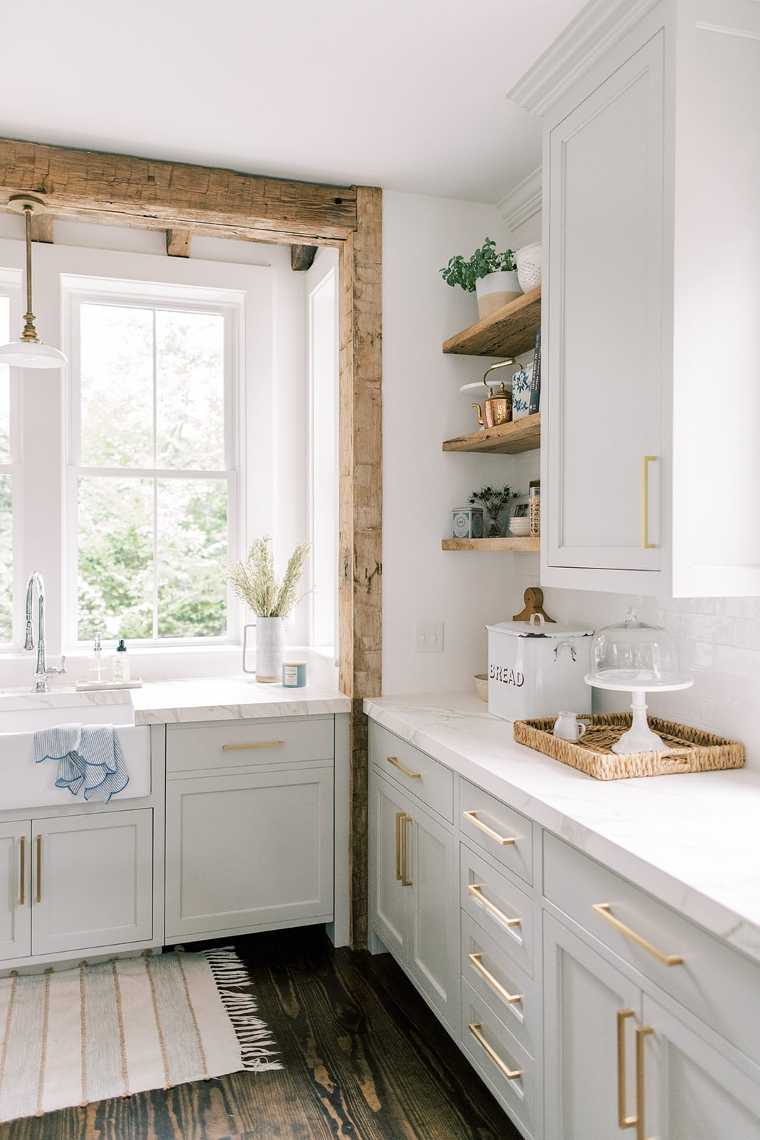 A farmhouse sink surrounded by gray cabinets and reclaimed barnwood beams.