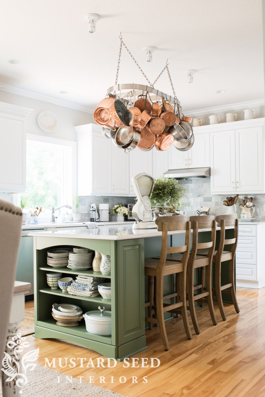 A farmhouse kitchen featuring a green island, white cabinets, and a pot rack with copper pots.