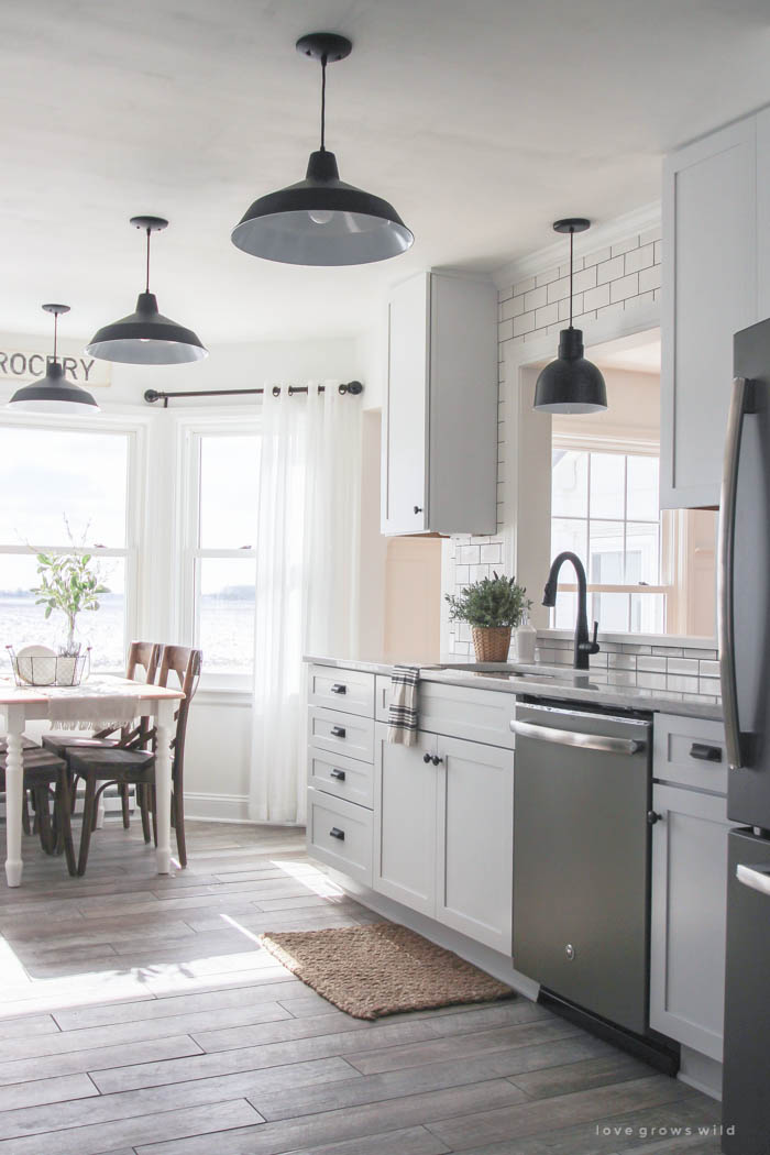 Farmhouse style kitchen with white cabinets and black light fixtures.