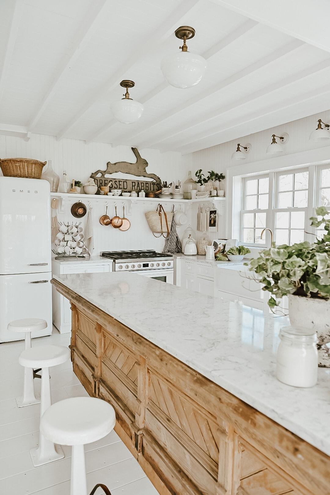 A white farmhouse style kitchen with an antique countertop island.