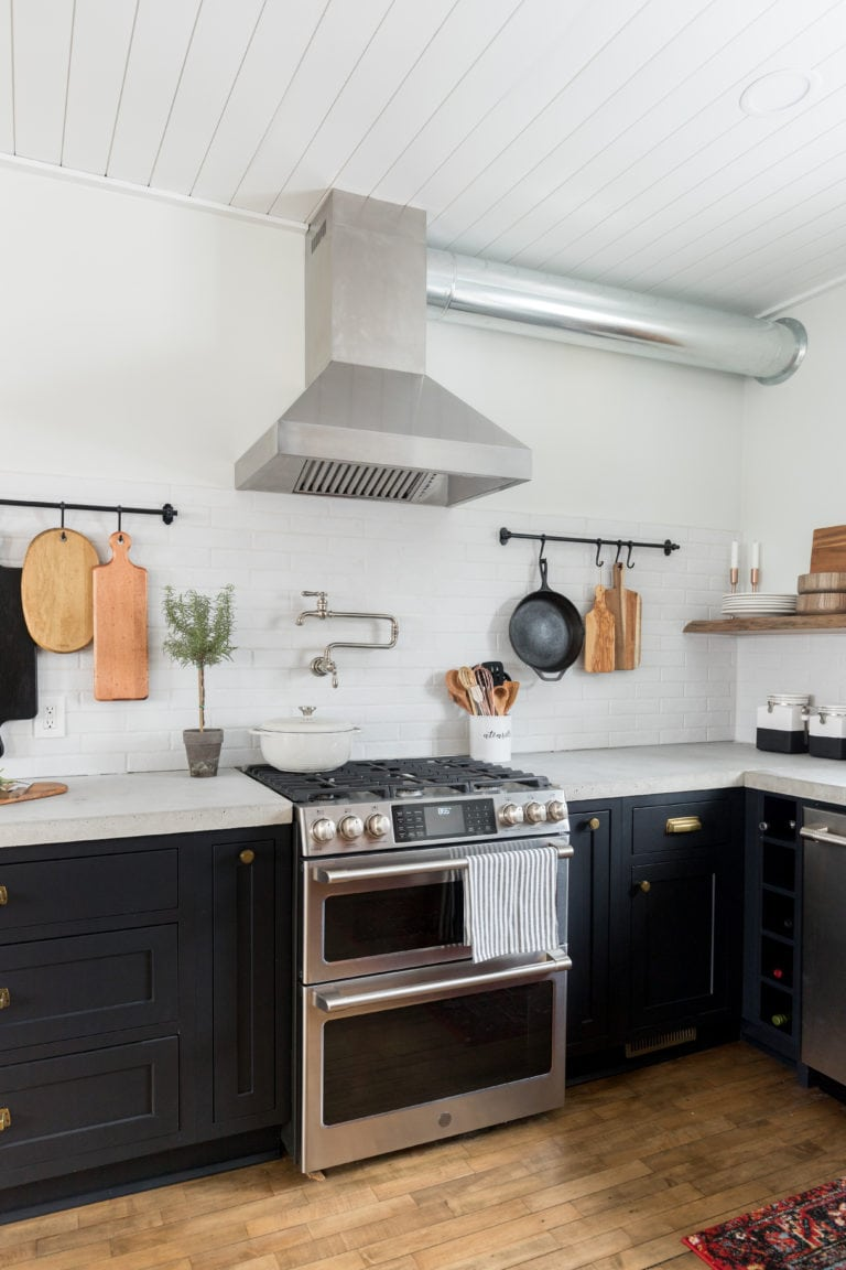 A farmhouse style kitchen with black cabinets and wood floors.