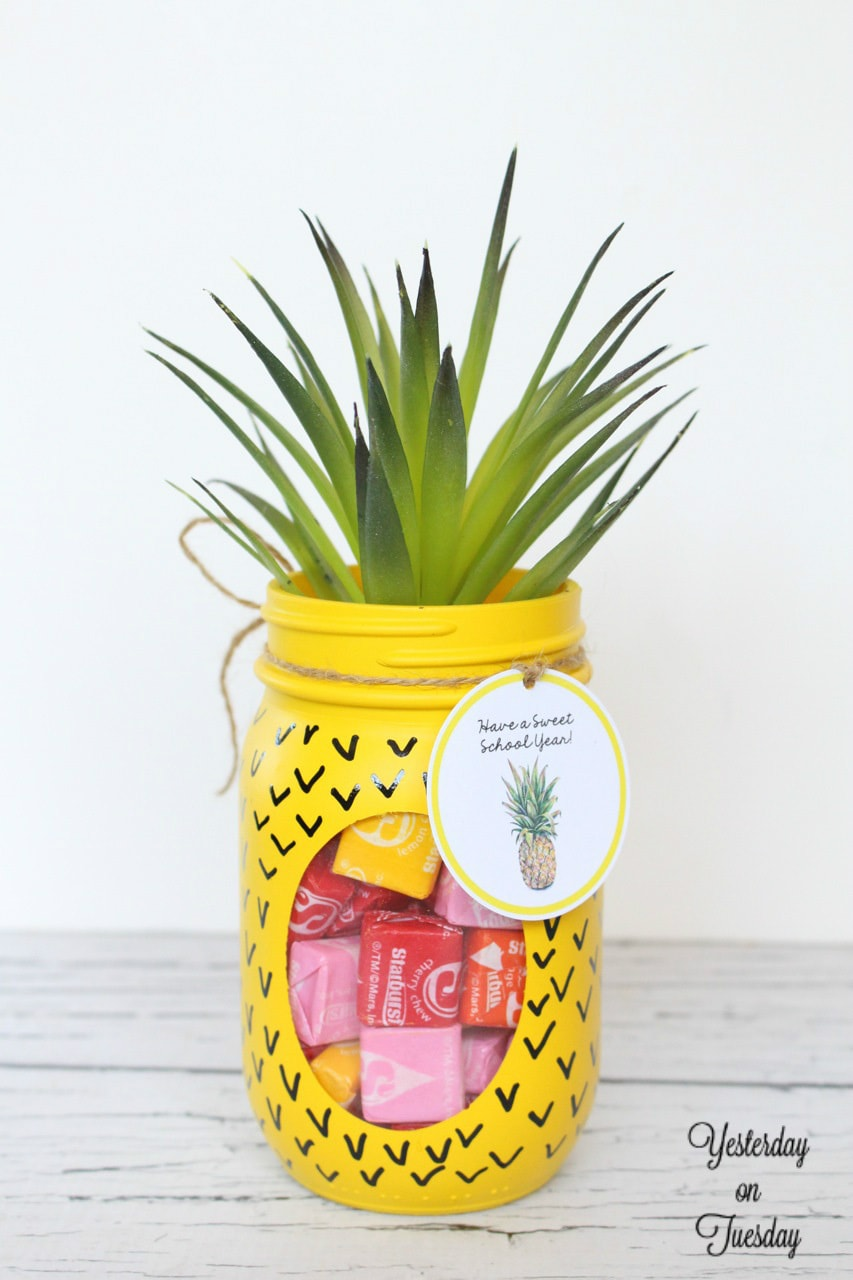 A mason jar turned into a pineapple with yellow paint and faux succulent on top.