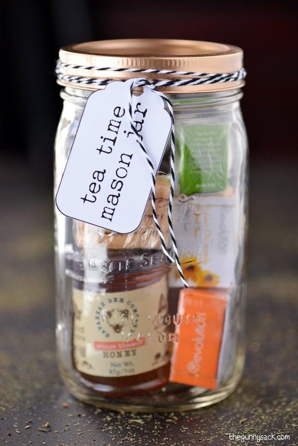 "A ""Tea Time"" mason jar filled with miniature tea samples and a jar of honey."