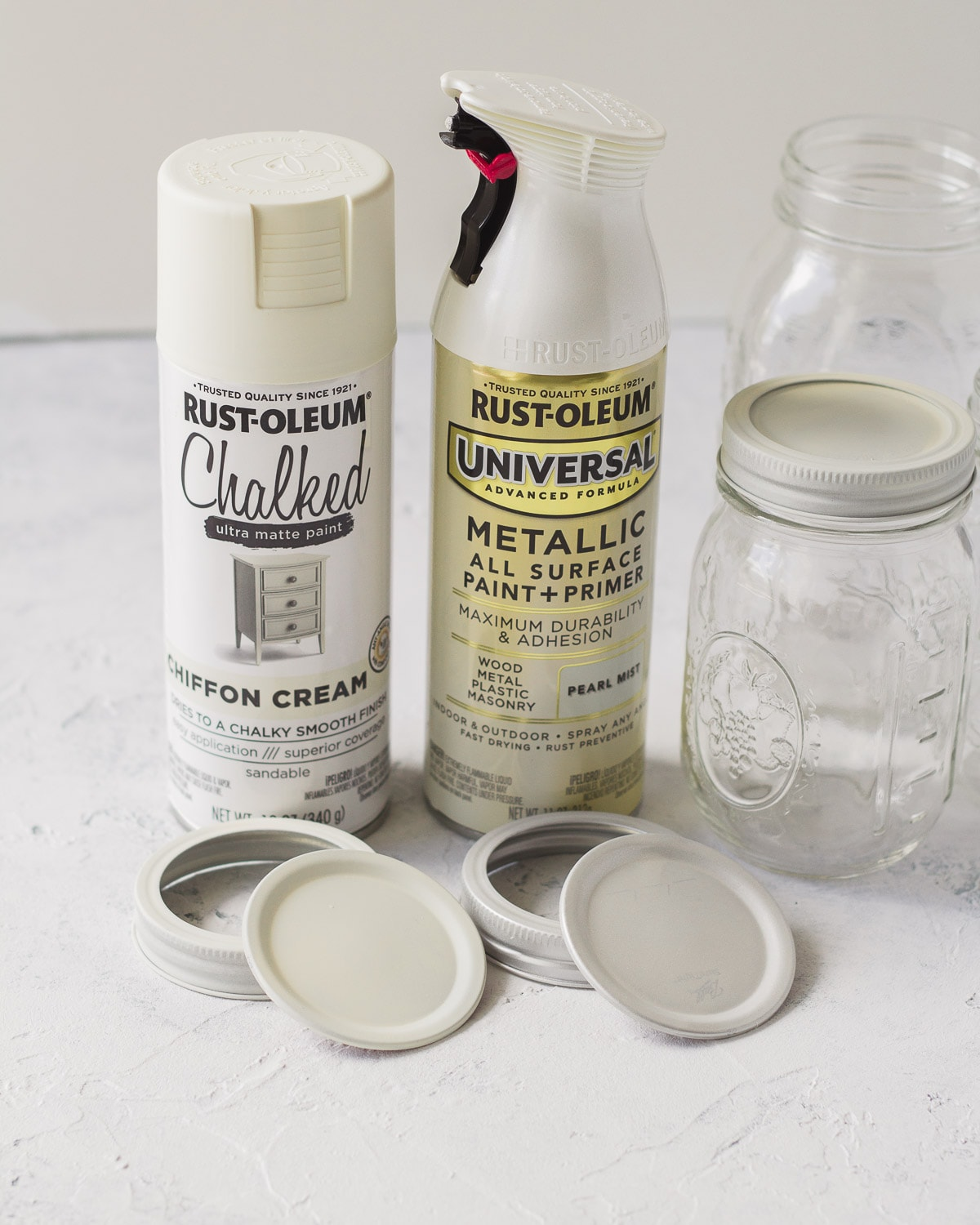 Two cans of white spray paint, spray painted mason jar lids, and mason jars.
