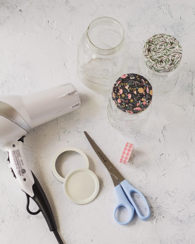 Hair dryer, mason jar lids, scissors, and washi tape mason jars.