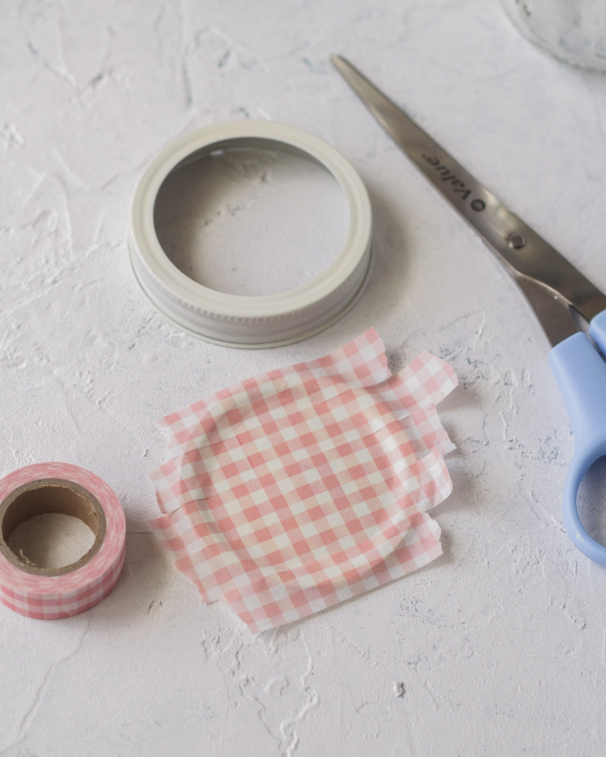 Glass jar lid covered with washi tape.
