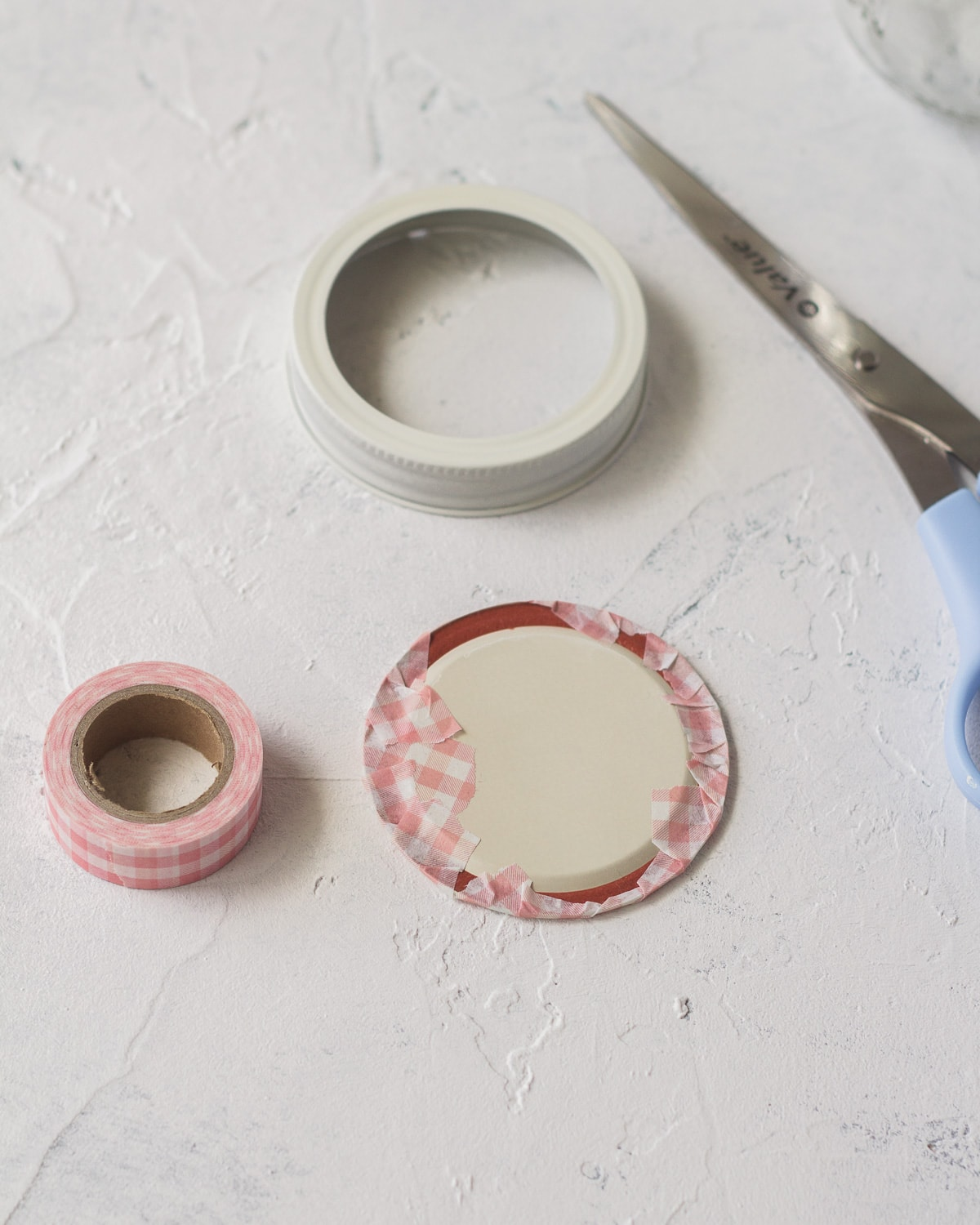 Wrapping a mason jar lid with tape.