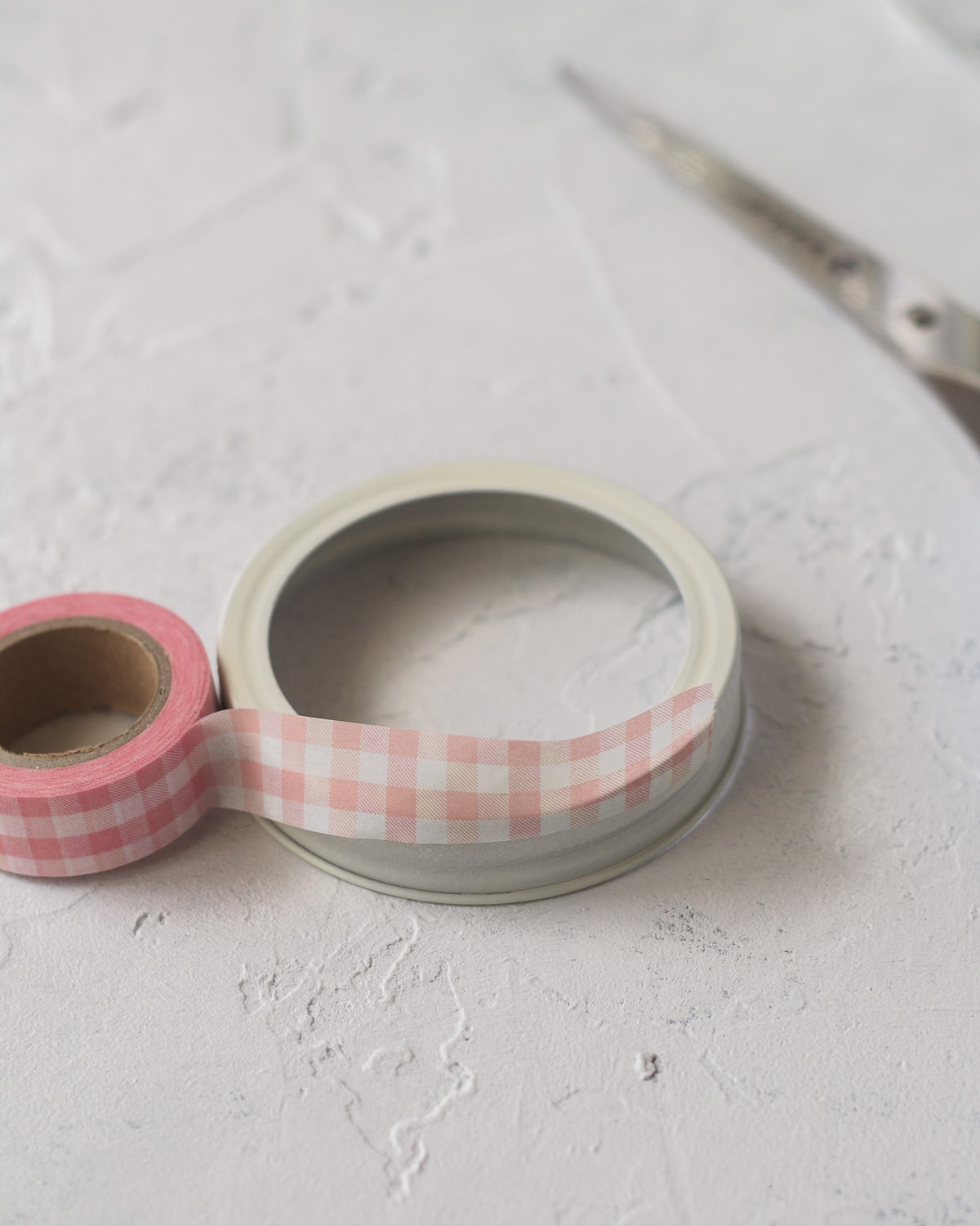 Wrapping a jar lid with pink washi tape.