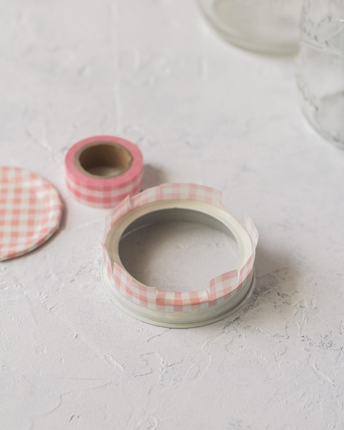 Jar lid wrapped with pink checked washi tape.