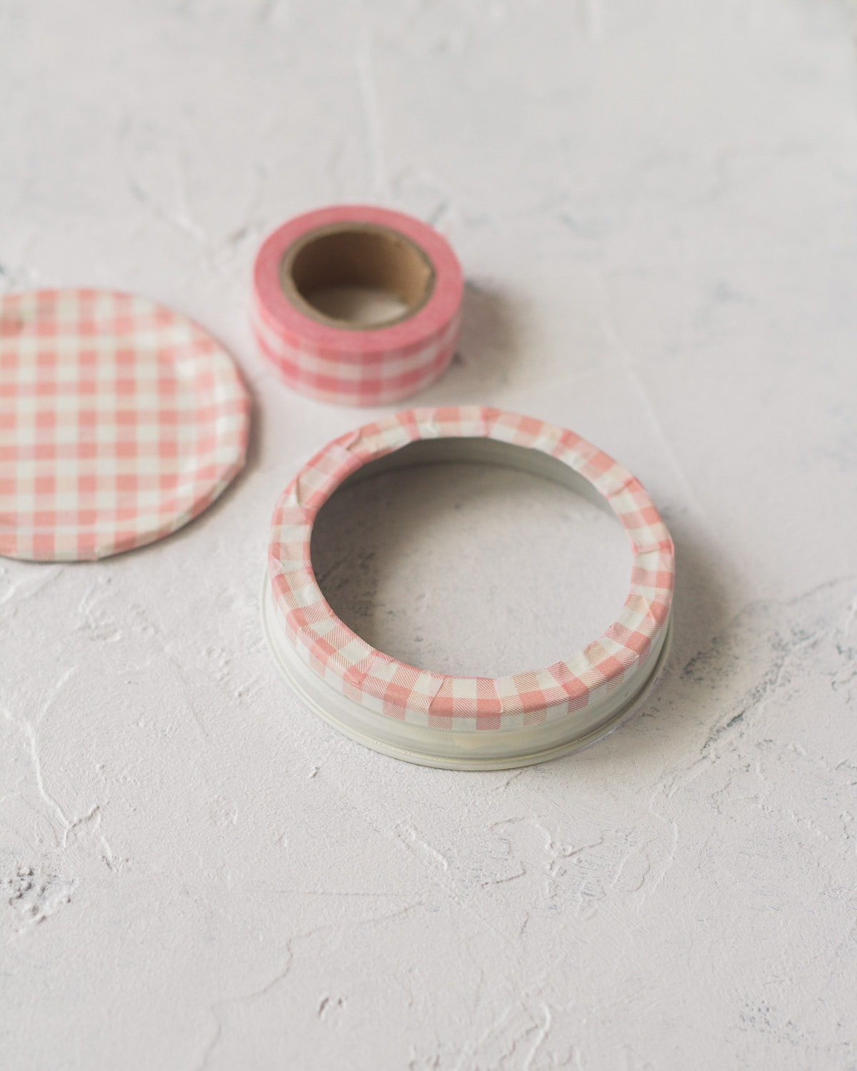 Glass jar lid covered in pink washi tape.