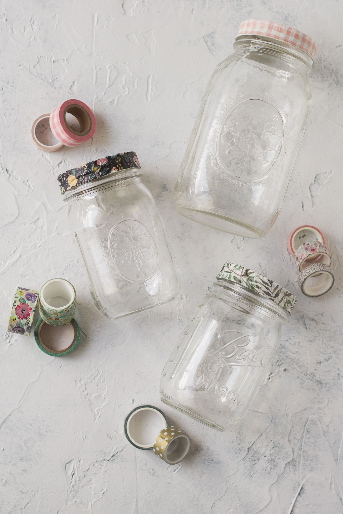 Three glass jars decorated with washi tape.