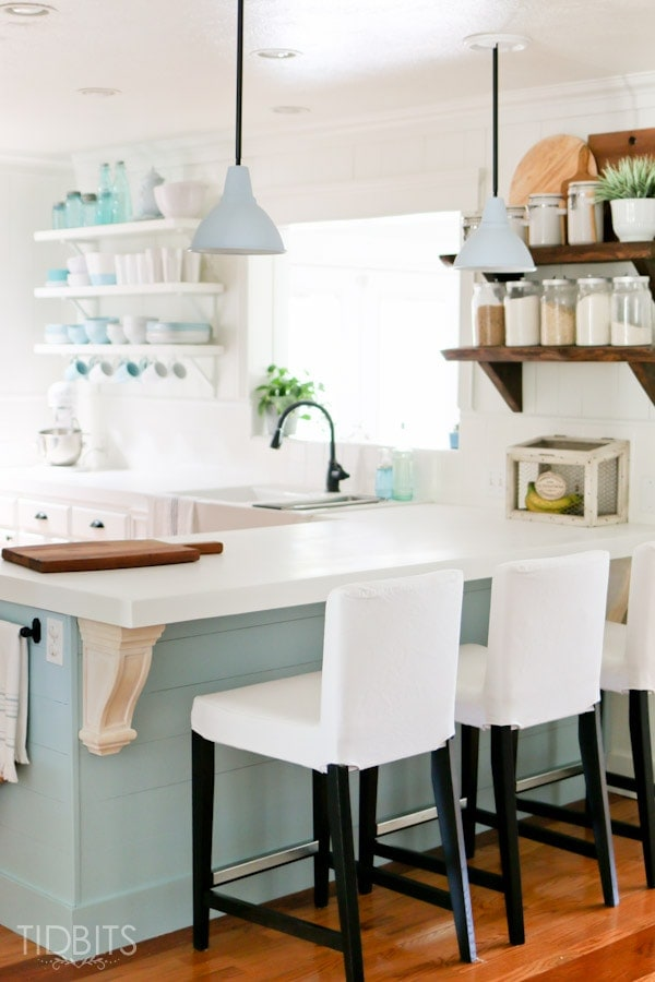 A kitchen with a bright blue/green island and decorative corbels.
