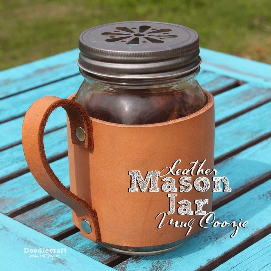 A mason jar decorated with a handmade leather mug coozie.