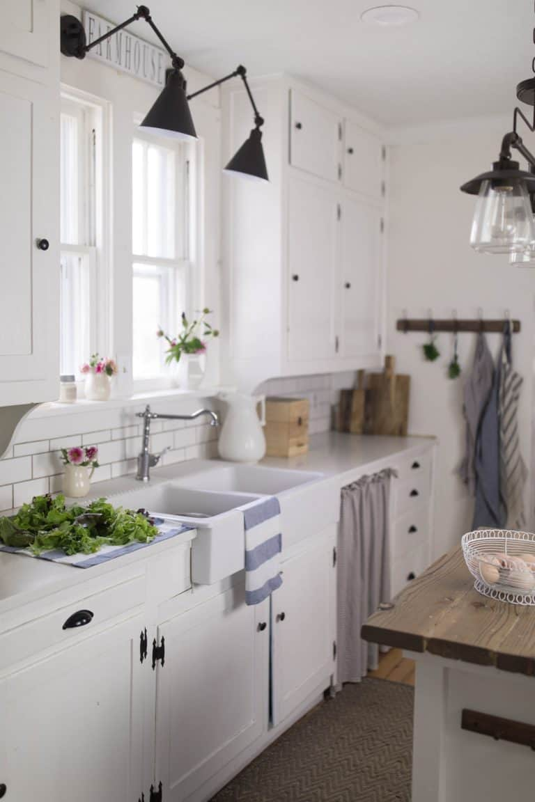 A white farmhouse style kitchen with summer flowers in white pitchers.