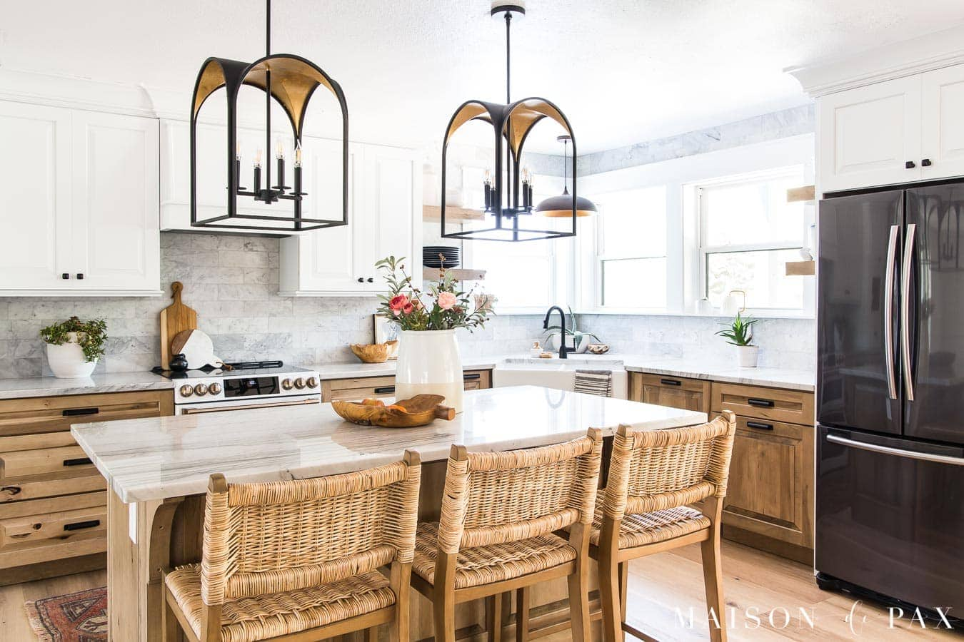 A stunning white and wood kitchen with wood cabinets, a white apron sink and statement light fixtures.