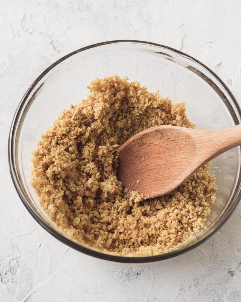 Stirring together sugar, graham cracker crumbs, and butter for a no-bake graham cracker crust.