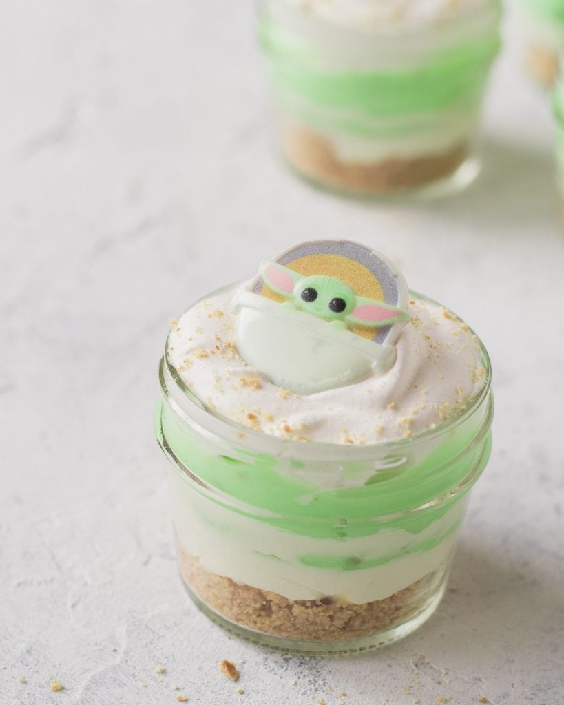 A mini pistachio dessert-in-a-jar topped with a Baby Yoda cupcake ring.