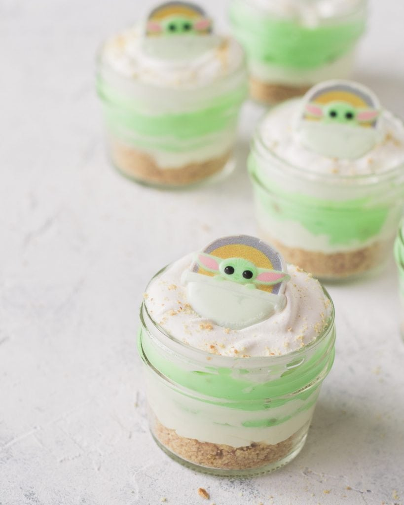 Mini pistachio desserts-in-a-jar topped with a Baby Yoda cupcake ring.
