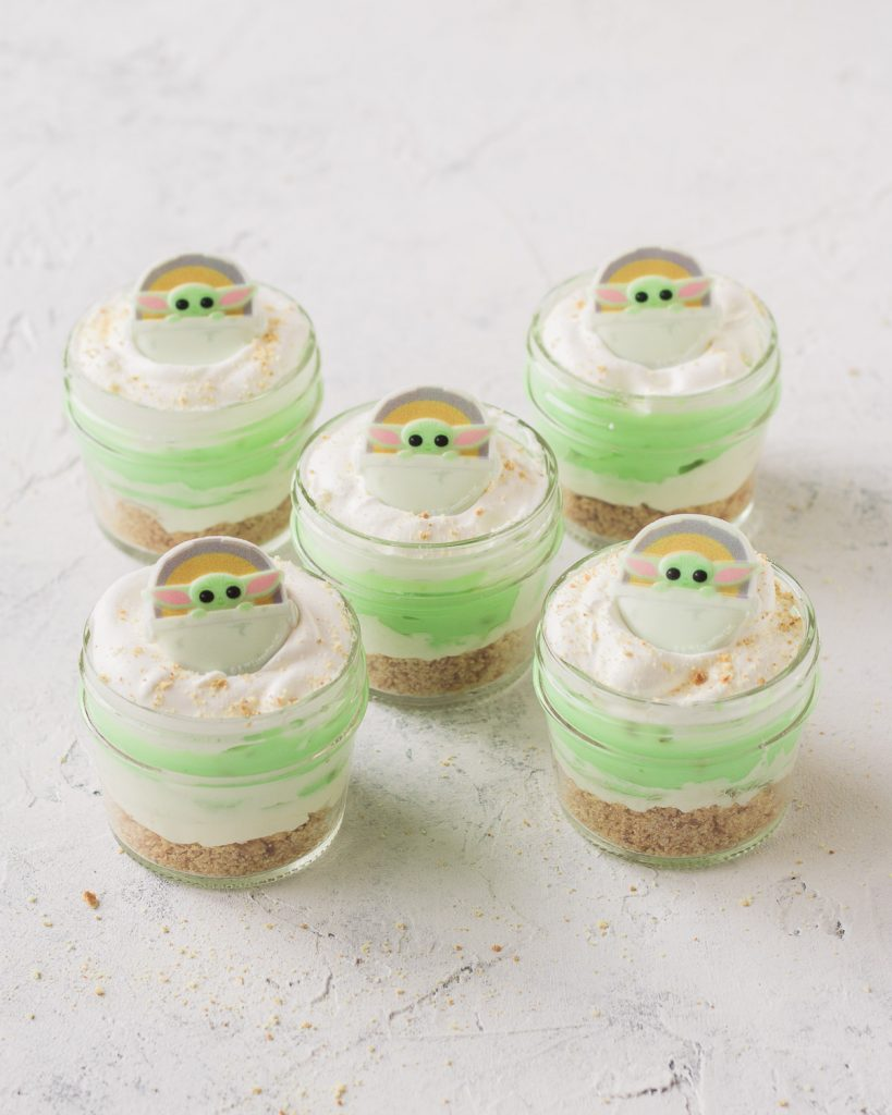 Five mini mason jar desserts layered with pistachio pudding, crust, and whipped topping and topped with Baby Yoda cupcake rings.
