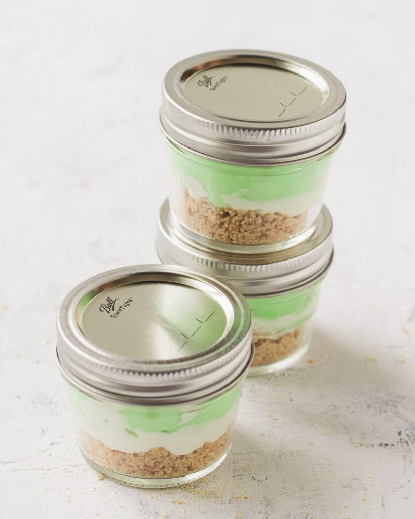 Three mason jar desserts with the lids on for travel.