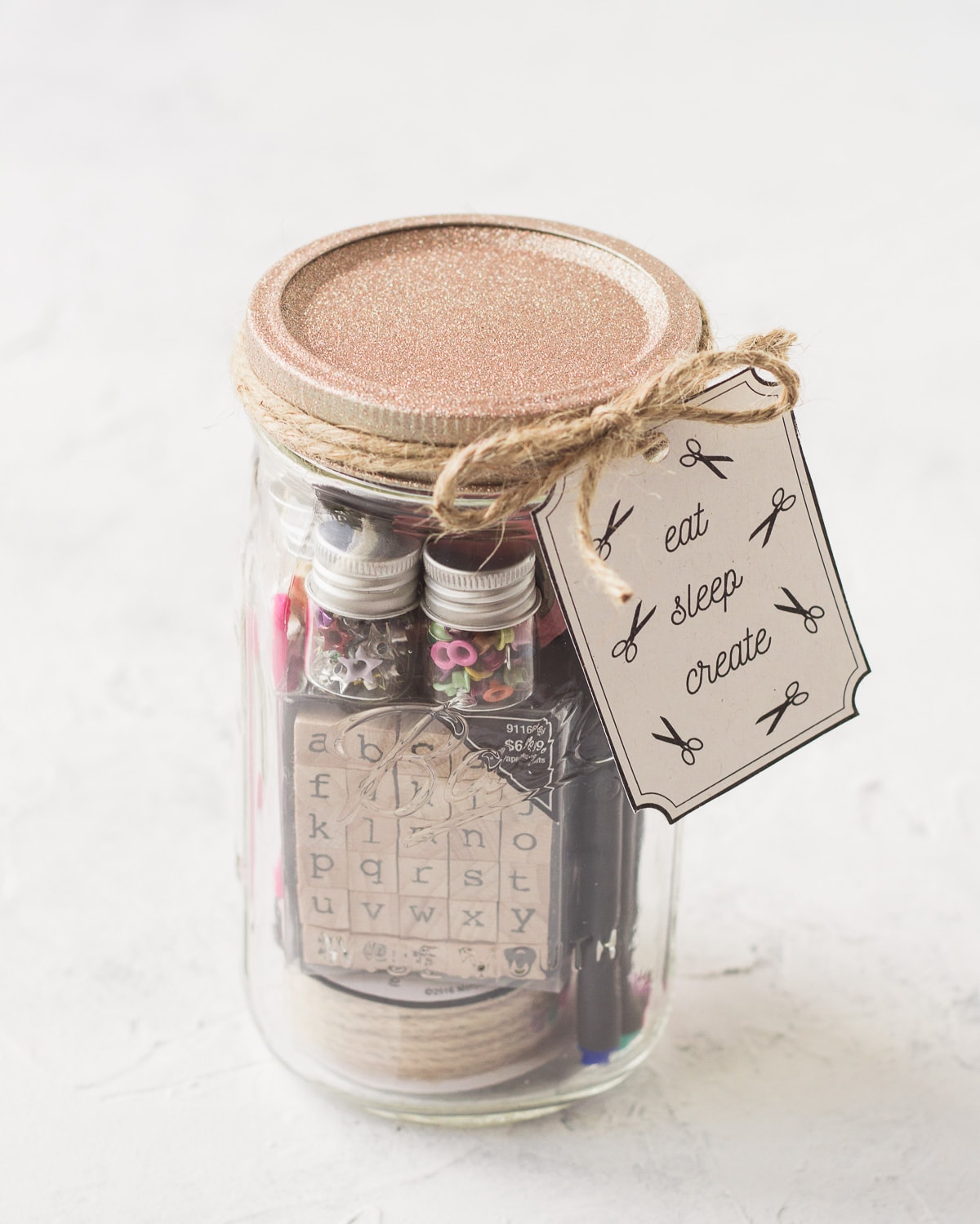 A mason jar gift filled with craft supplies and tied with a handmade gift tag.