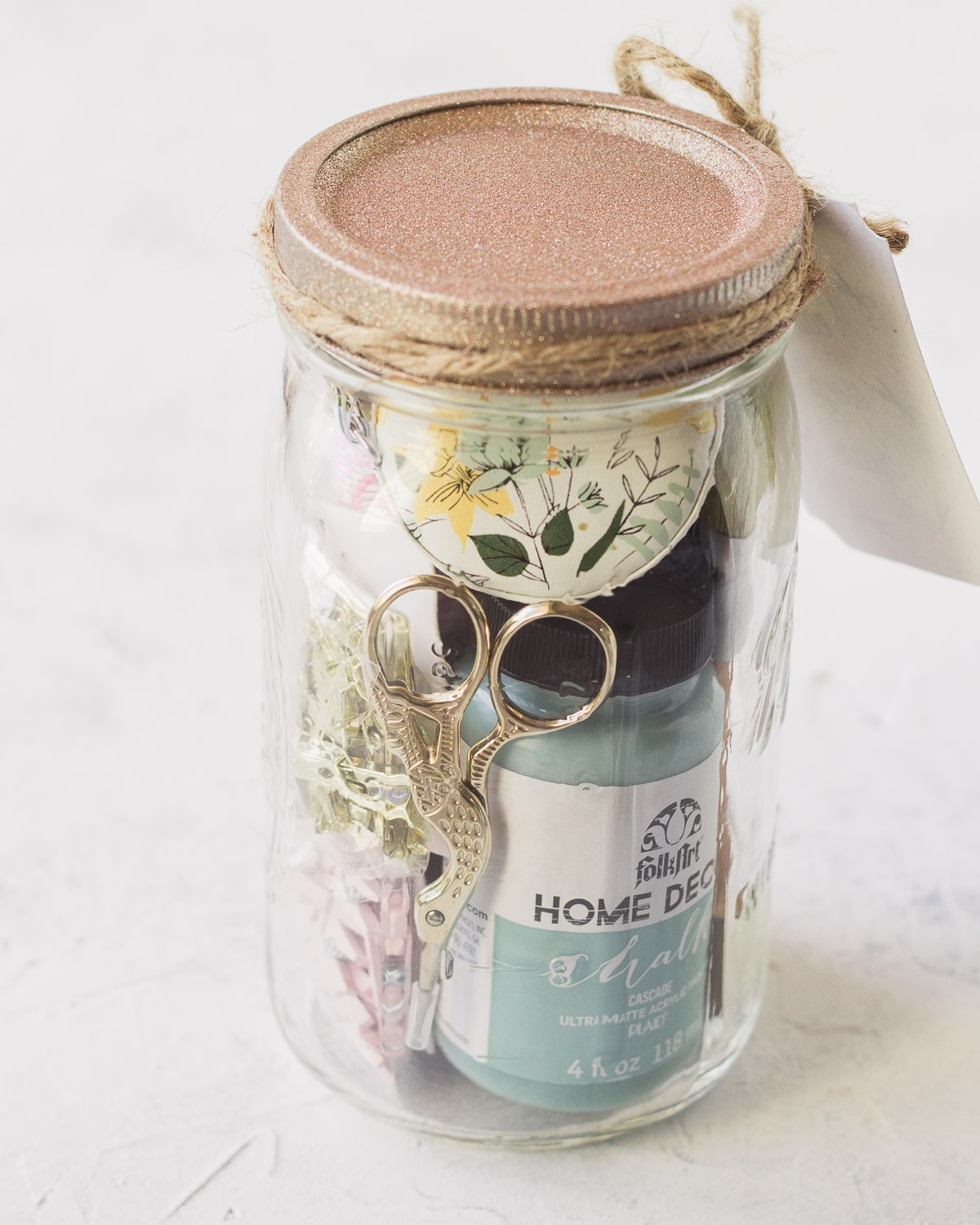 Embroidery scissors, chalk paint, and various craft supplies in a mason jar.