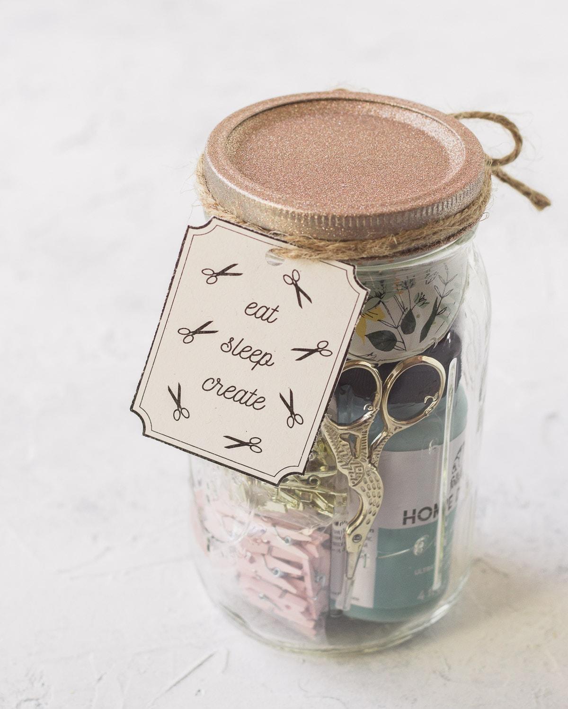 A craft supplies mason jar with a handmade gift tag.