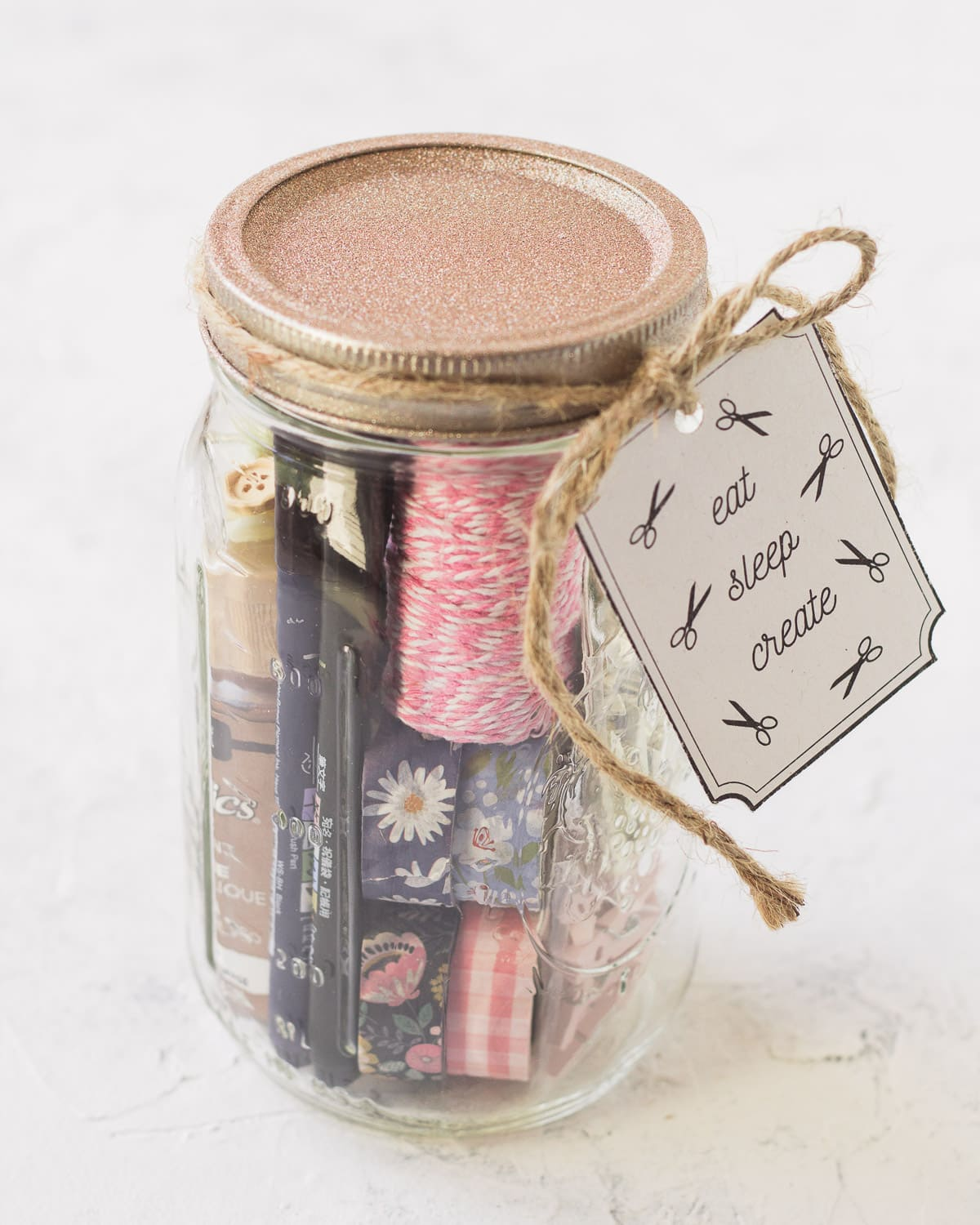 Washi tape and colorful twine in a mason jar with a gift tag.