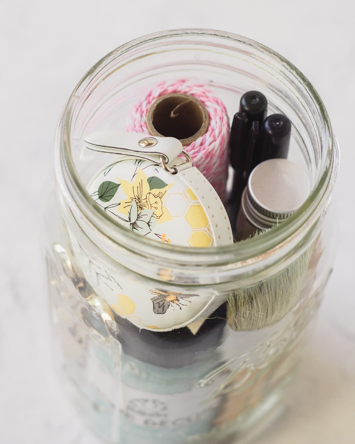 A tape measure and craft supplies packed into a mason jar.