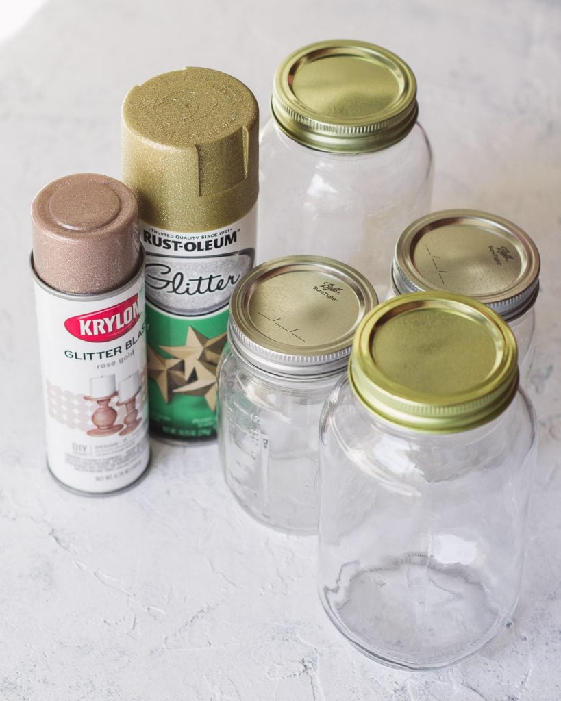 A selection of glass jars and glitter spray paints.