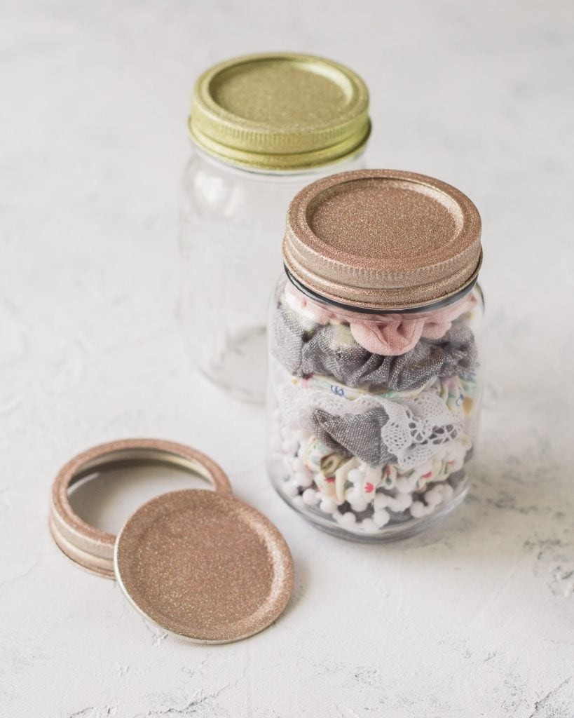 Glass jar filled with scrunchies and a glitter-covered lid.