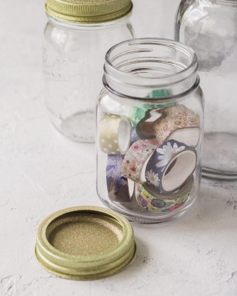 A glittery gold mason jar lid and a jar full of floral washi tape.