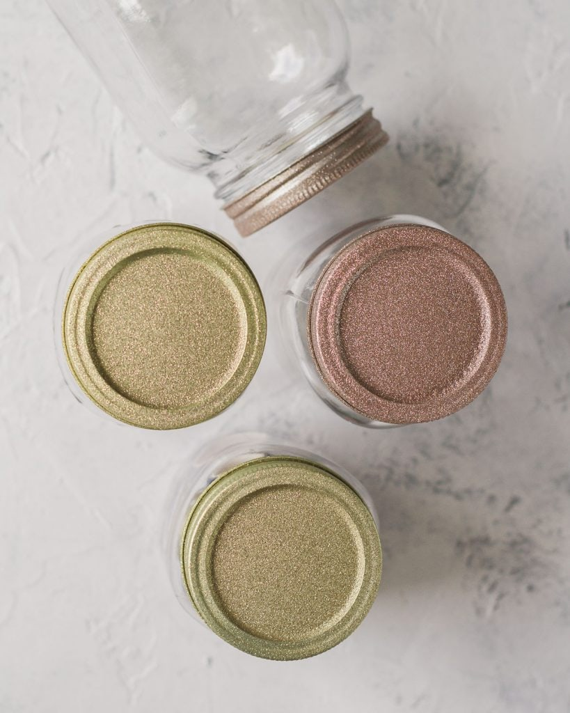 Four mason jar lids covered in gold and rose gold glitter spray paint.