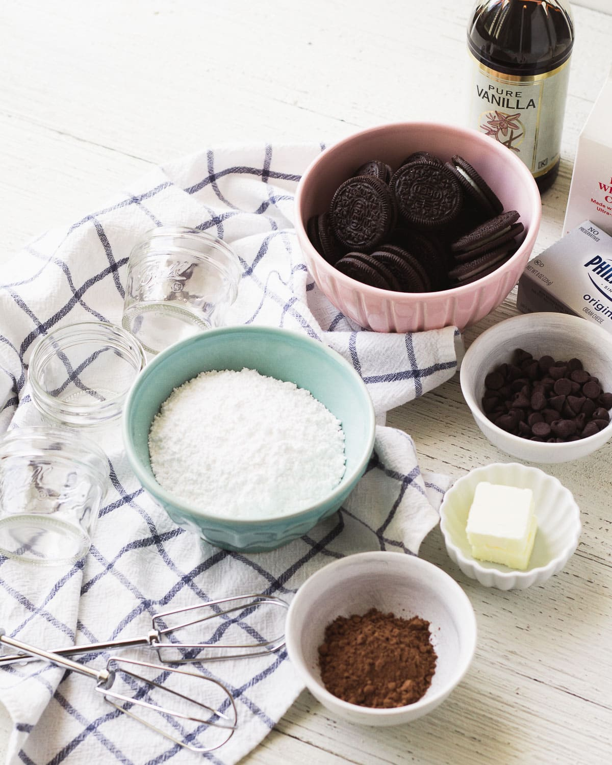 Bowls filled with various ingredients: chocolate sandwich cookies, cocoa powder, butter, and powdered sugar and more.