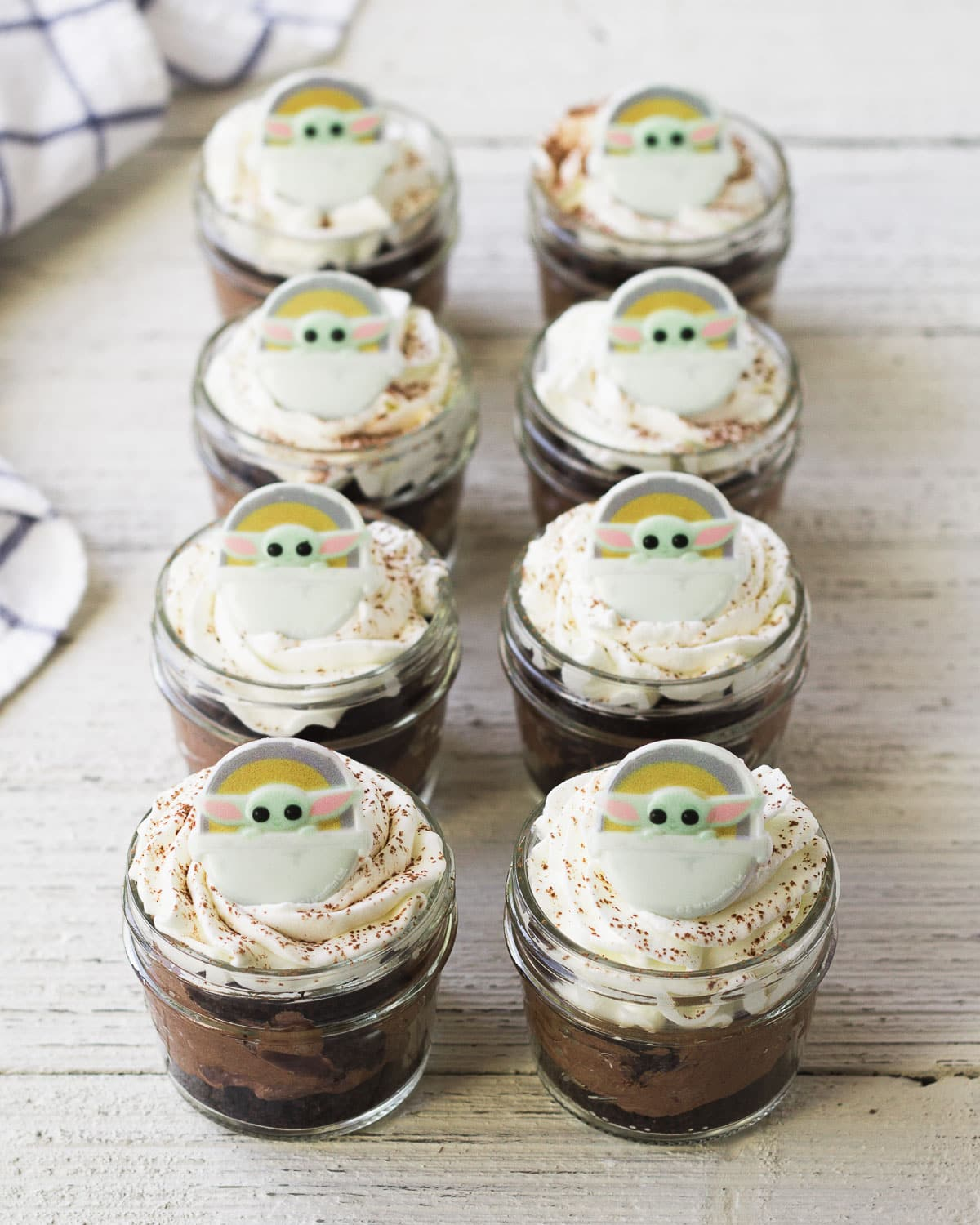 Eight mini layered chocolate desserts topped with Baby Yoda decorations.