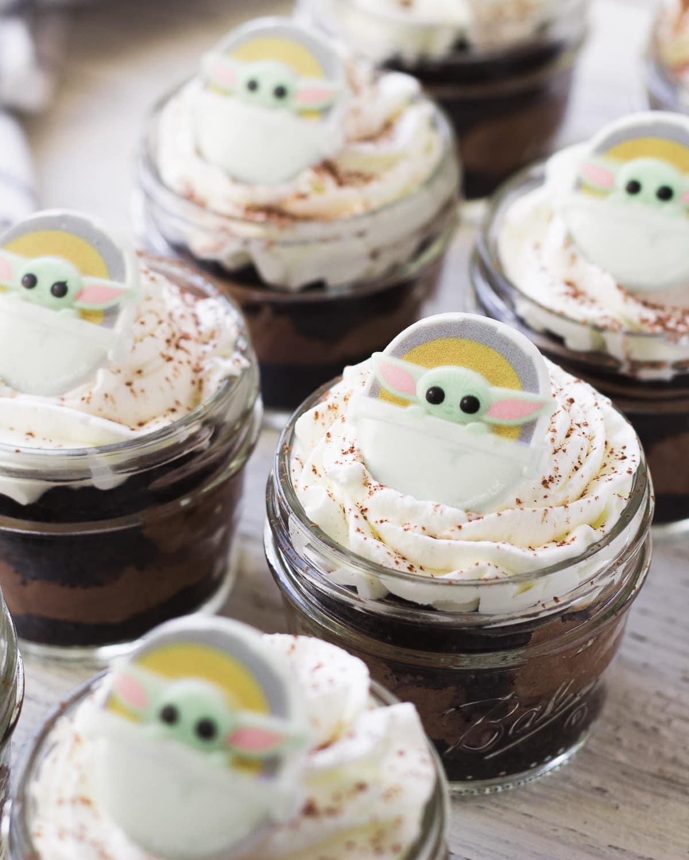 Mason jar chocolate desserts topped with Baby Yoda decorations.