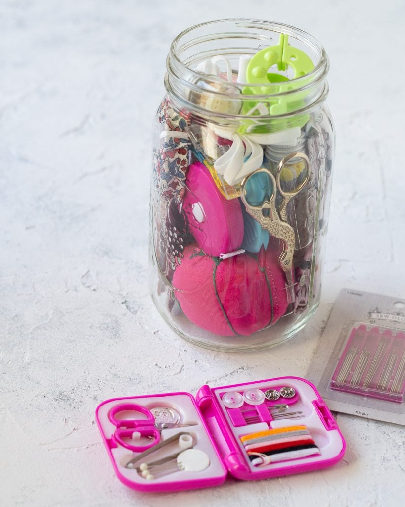 A miniature sewing kit in front of a larger mason jar sewing kit.