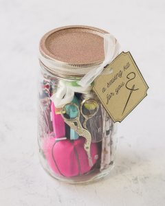 A sewing kit mason jar filled with a pincushion, embroidery scissors, fabric, and more.