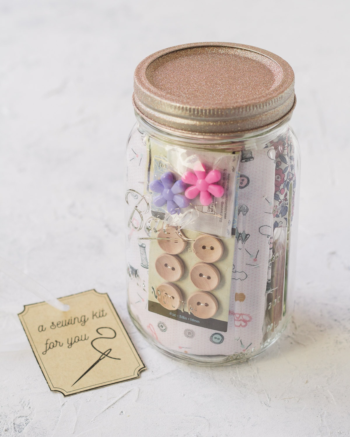 A mason jar sewing kit filled with buttons, fabric, and more.