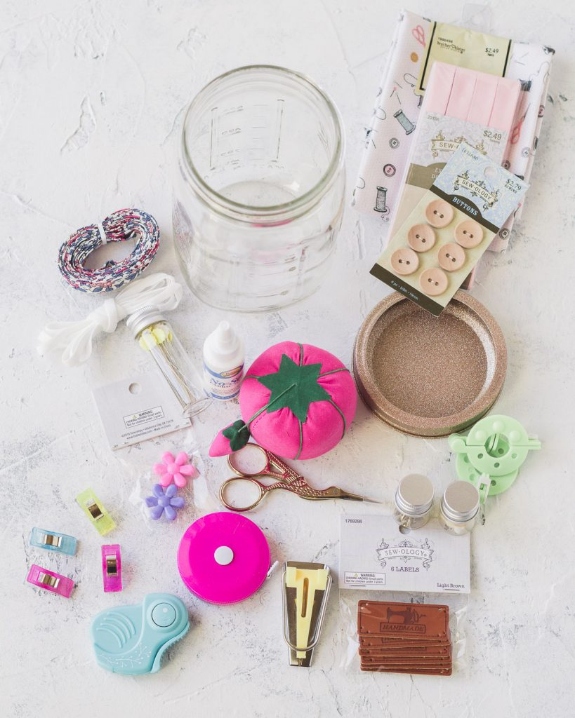 """Supplies to make a mason jar sewing kit including a mini rotary cutter, a retractable tape measure, bias tape maker, """"handmade"""" labels, and more."""