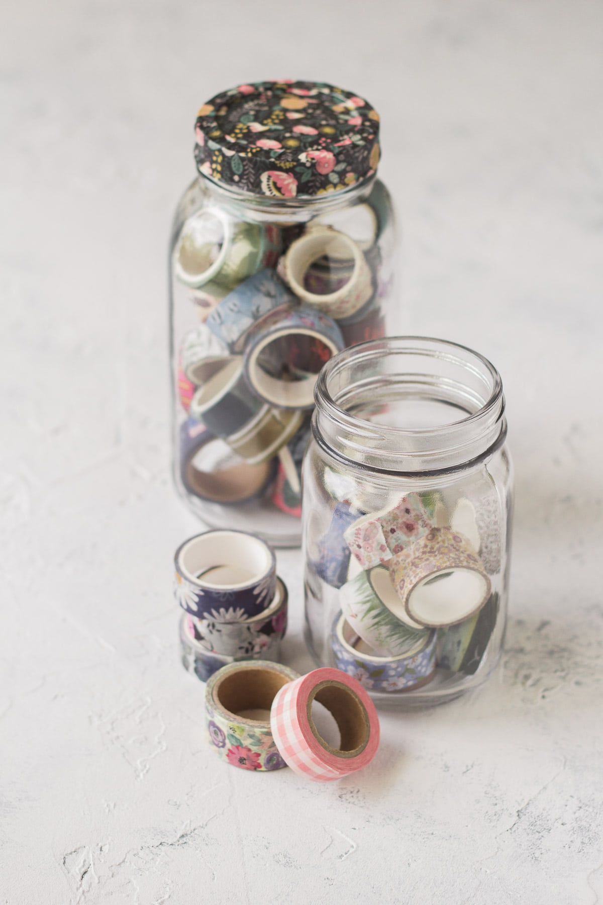 Two mason jars filled with washi tape with more spools surrounding the jars.