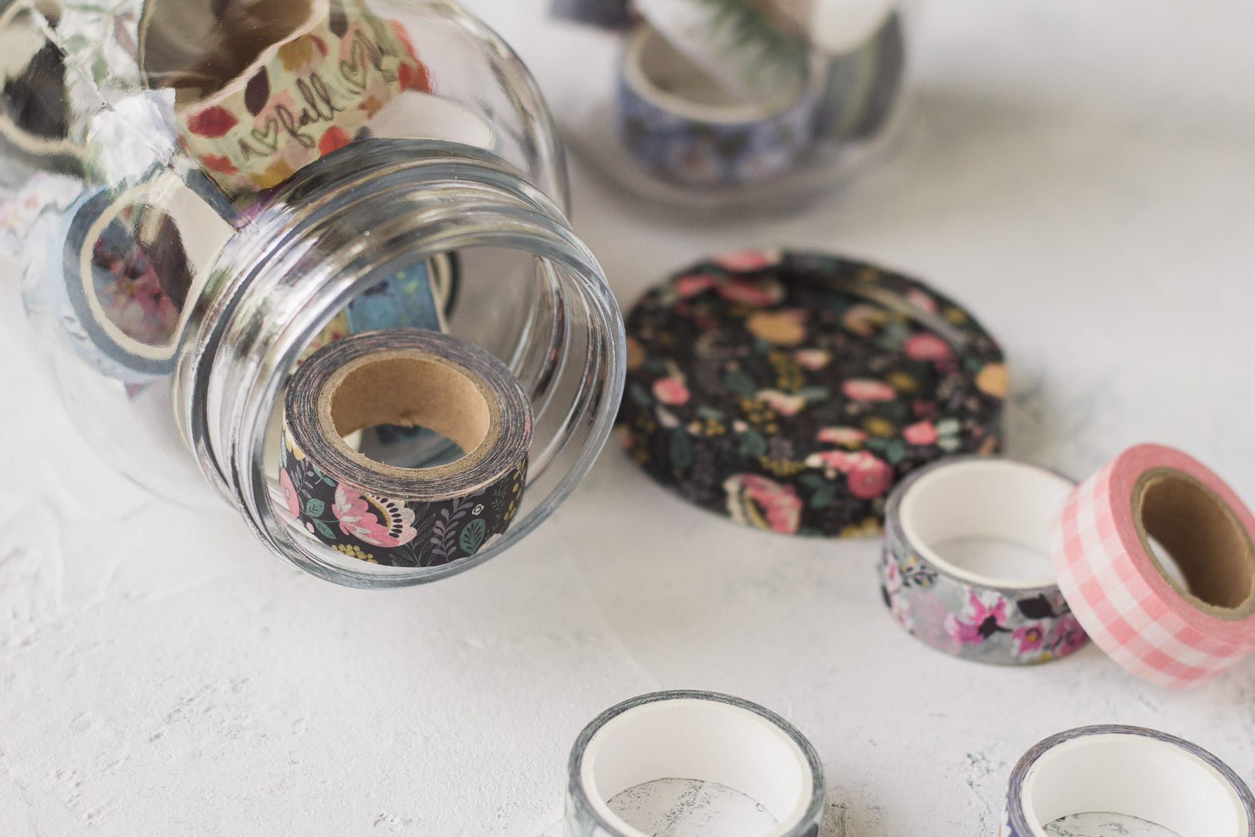 Washi tape in a mason jar with more spools surrounding.